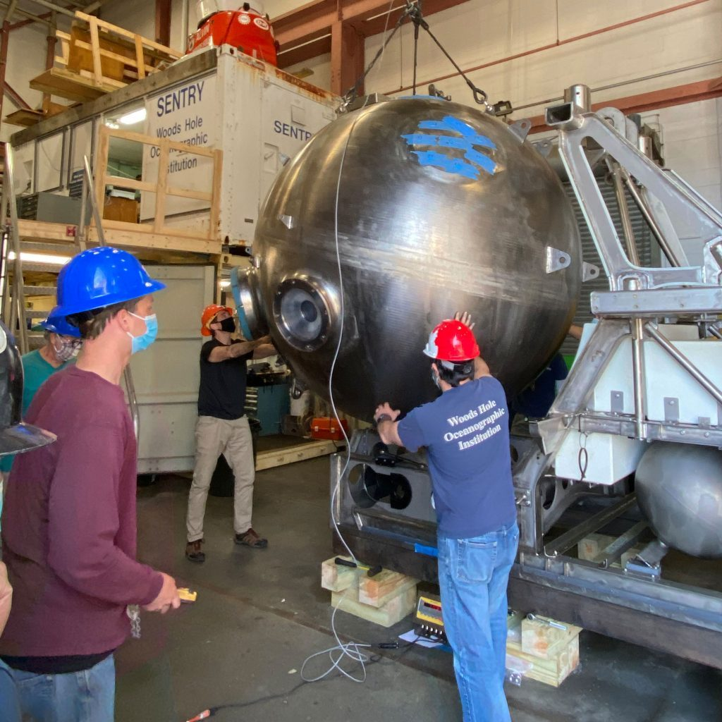Rod Catanach, Fran Elder, Bruce Strickrott, and Anthony Tarantino lift the 11,000 pound sphere from the frame. All the welds on the sphere will be ultrasonically tested and the surface will be painted with a dye and developer that will reveal even small cracks. (Photo by Drew Beweley © Woods Hole Oceanographic Institution)